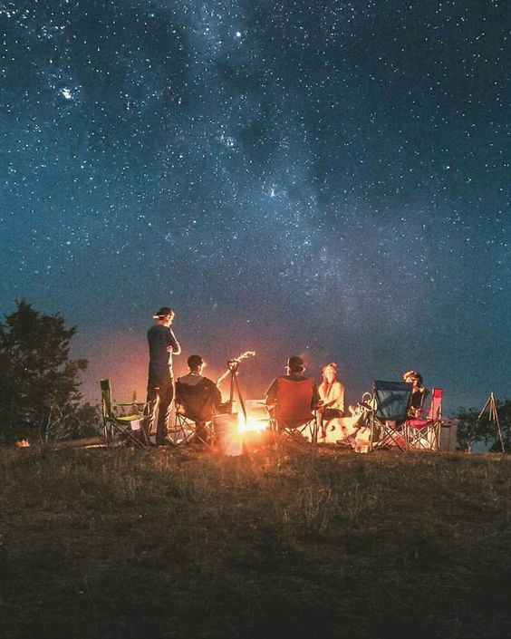 Group sitting around a campfire under a starry sky